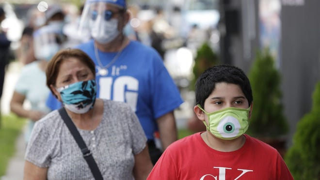 People, social distancing and wearing masks to prevent the spread of the new coronavirus, wait in line at a mask distribution event Friday  in a COVID-19 hotspot of the Little Havana neighborhood of Miami.