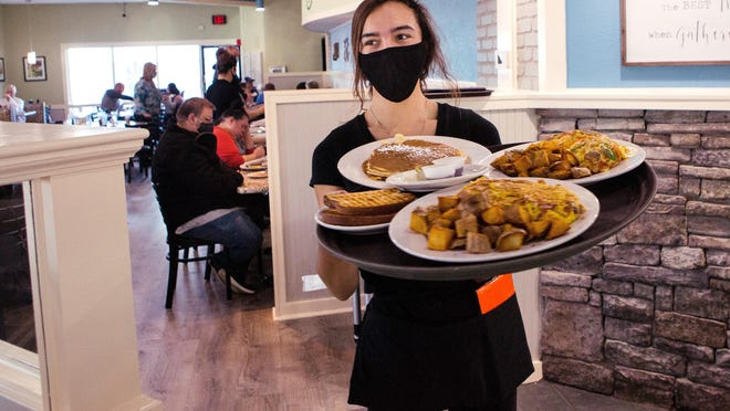 Jaina Brandon brings a tray of food to customers at Sweet Basil Cafe in Springfield. The Sangamon County Department of Public Health announced that bars and restaurants can be open for indoor dining at 25% capacity beginning Sunday.