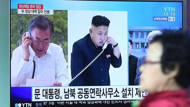 A woman walks past a news screen showing file footage of South Korean President Moon Jae-in, left, and North Korean leader Kim Jong Un, center, at a railway station in Seoul on April 25, 2018. Kim Jong Un is set to walk across the Demilitarized Zone on April 27, for a historic summit with Moon, the highest-level encounter yet in a whirlwind of nuclear diplomacy.