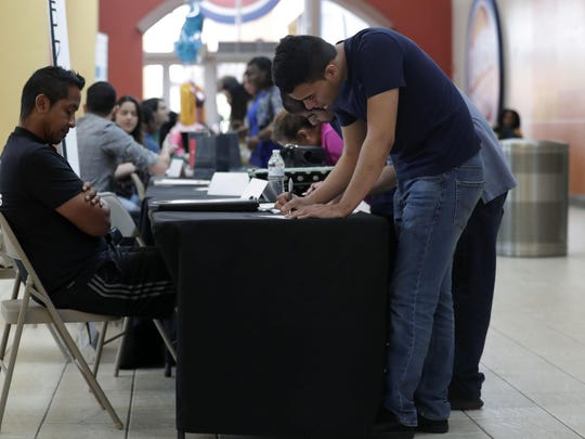 FILE - In this Oct. 1, 2019, file photo Billy Ramos, right, fills out a job application with Adidas during a job fair at Dolphin Mall in Miami. On Friday, Nov. 1, the U.S. government issues the October jobs report. (AP Photo/Lynne Sladky)
