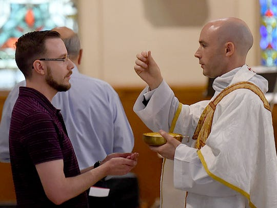 Rev. Benjamin James Pitre administers Holy Communion