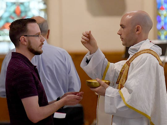 Rev. Benjamin James Pitre administers Holy Communion during his first Solemn Mass of Thanksgiving Sunday at St. Landry Catholic Church.