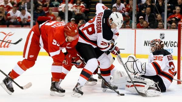 Detroit Red Wings forward Johan Franzen, left, tries to shoot as New Jersey Devils defenseman Damon Severson (28) defends in front of goalie Cory Schneider Friday night.