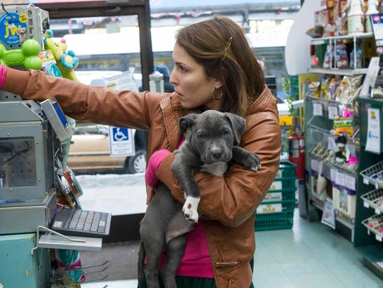 Noomi Rapace holds Rocco, played by three pit bull
