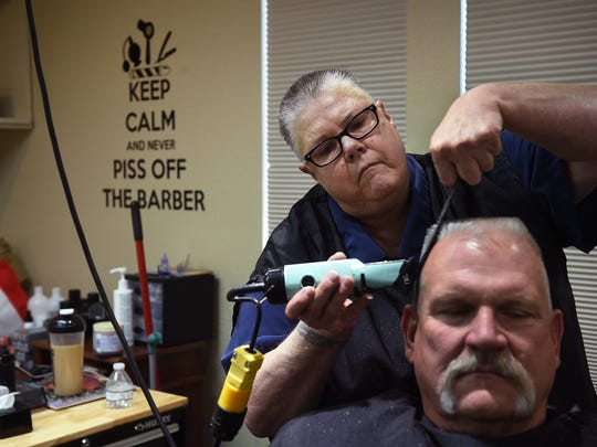 Dee Goodman of Old West Barber Shop gives a client a haircut at her old Reno shop on July 29, 2016.
