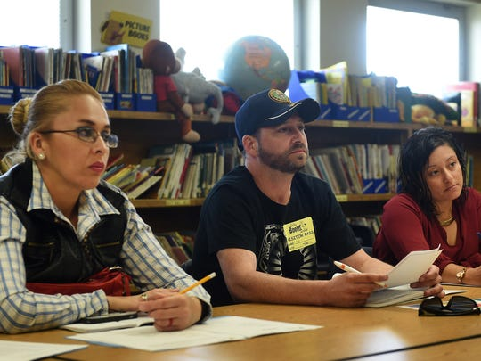 From left, concerned parents Veronica Casillas, Terry Bradford and Lidia Rangel listen during a walking tour and group discussion with regards to overcrowding at Booth Elementary School.
