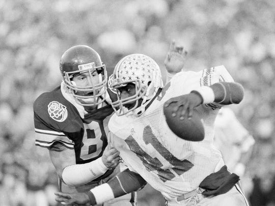 USC Trojans linebacker Duane Bickett (80), in dark jersey, corrals Ohio State Buckeyes tailback Keith Byars (41) for a loss during late fourth quarter of Rose Bowl game in Pasadena, California, on Tuesday, Jan. 2, 1985. The Trojans won, 20-17. (AP Photo)