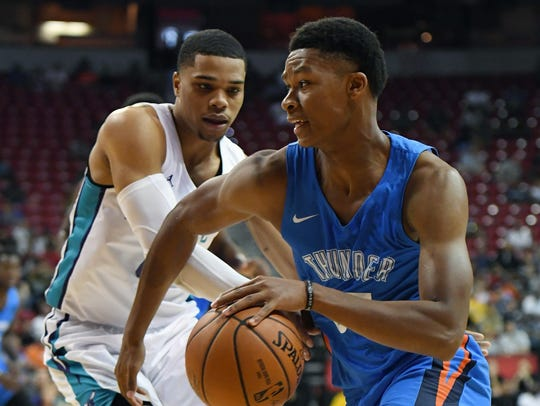 PJ Dozier of the Oklahoma City Thunder drives against Miles Bridges of the Charlotte Hornets.