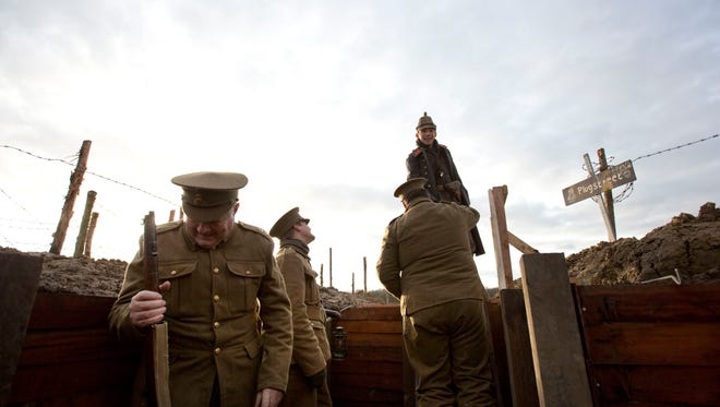 Re-enactors, from various living history groups, are dressed in World War I British and German uniforms as they re-enact the 1914 Christmas Truce in Ploegsteert, Belgium on Saturday, Dec. 20, 2014. During that first Christmas Day in World War I, something magical happened. Soldiers who had been killing each other by the tens of thousands for months climbed out of their muddy trenches to seek a shred of humanity amid the horrors of war. Hands reached out across the narrow divide, presents were exchanged, and in Flanders Fields a century ago, a spontaneous Christmas truce briefly lifted the human spirit. (AP Photo/Virginia Mayo)