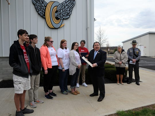 State Rep. Tim Schaffer hands a resolution to members of the Lancaster High School marching band to recognize the group for its fundraising efforts for Mothers Against Drunk Driving Walk Like MADD event.