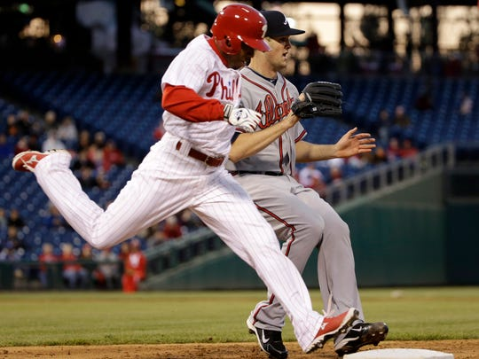 The Phillies' Ben Revere safely reaches first base as Atlanta Braves starting pitcher Alex Wood runs to cover the bag.