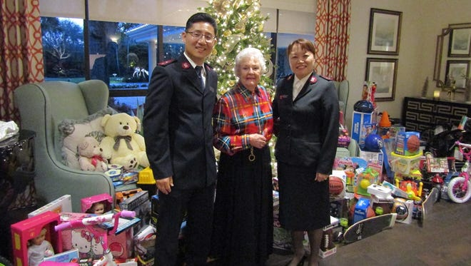 Piper's Landing Angel Tree coordinator Jeanne Lambdin, center, stands with Salvation Army Captains Samuel and Christine Kim in front of the tree surrounded by gifts for children in need.