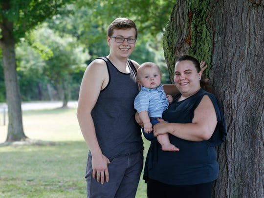 Former Walmart employee Leigha Klopp, 21, of Medina, Orleans County, with her eleven-month-old son Oliver Kenward, and fiancé Jakob Kenward, 22, at a park in Albion. Klopp is part of a lawsuit filed against the retailer alleging the company discriminates against pregnant women.