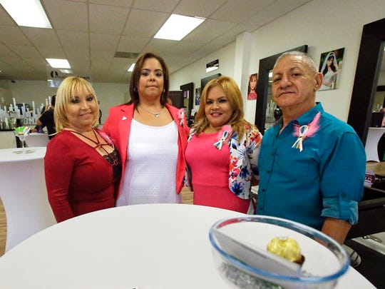 Family members of Pulse nightclub shooting victim Juan Rivera Velazquez, from left, Agelita Velazquez, his mother, sister Jessica Silva, cousin Rosa Velazquez and father Ramon Rivera, gather for a photo at the re-opening of the D'Magazine Salon Thursday, Dec. 8, 2016, in Orlando, Fla.