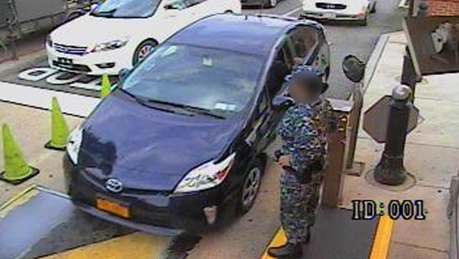 Aaron Alexis drives his rental car, a blue Toyota Prius, through a security gate at the Washington Navy Yard.