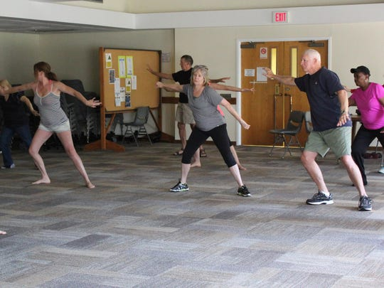 Tai Chi instructor John Mazetis (left) guides participants through the flowing movements of Tai Chi.