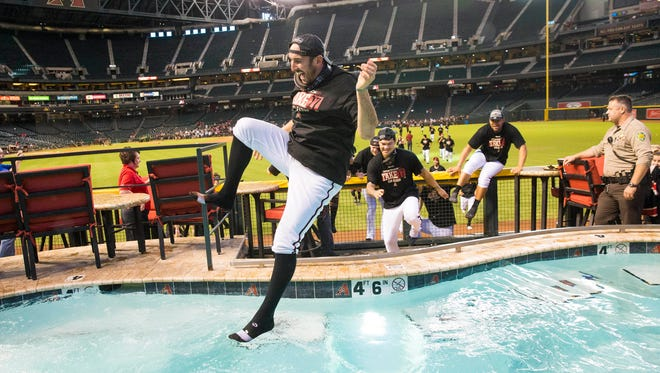 Arizona Diamondbacks shortstop Adam Rosales (9) jumps into the pool while celebrating a playoff berth at Chase Field in Phoenix on Sept. 24, 2017.