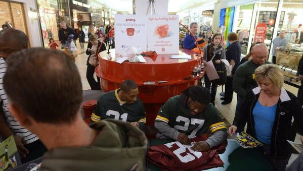 Green Bay Packers running back Eddie Lacy (27) and safety Ha Ha Clinton-Dix (21) sign autographs at the Salvation Army's Big Red Kettle in Bay Park Square mall on Monday in Ashwaubenon.