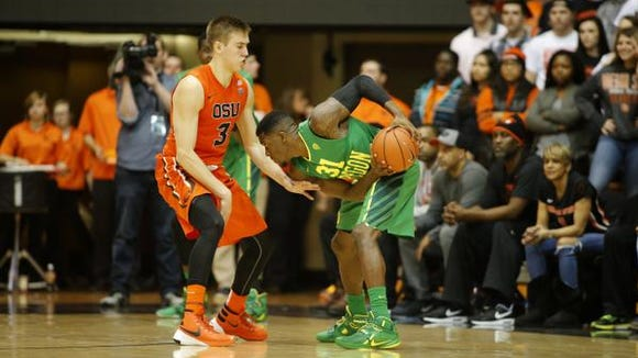 Oregon State's Tres Tinkle (3) and  Oregon's Dylan Ennis (31) in the second half of an NCAA college basketball game, in Corvallis, Ore., on Sunday, Jan. 3, 2016. (AP Photo/Timothy J. Gonzalez)