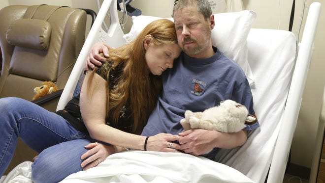 Jason Garcia, 42, holds his stuffed animal named Grumpy Cat as he sits with his wife, Heather, in his hospital bed in February at Milwaukee's Froedtert Hospital.