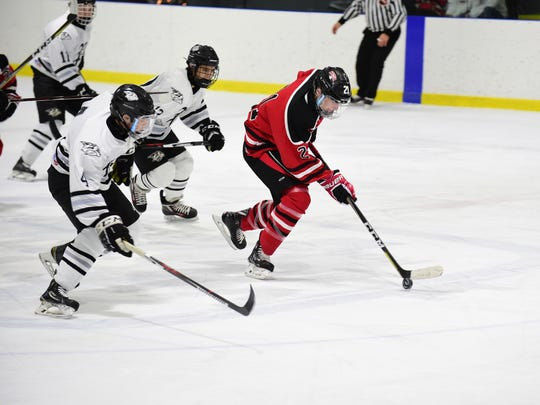 Livonia Churchill's Connor Burnette (21) skates with the puck while Plymouth's Shane Aigner (12) and Joey Closser (4) give chase.