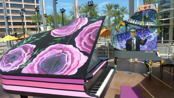 The floral design on the baby grand piano at left was painted by Phoenix mural artist Lauren Lee with the help of kids from the Boys and Girls Club Grant Woods Branch. At right is a piano whose lid was transformed by lead artist William Barnhart, a docent of the Mesa Contemporary Arts Museum.