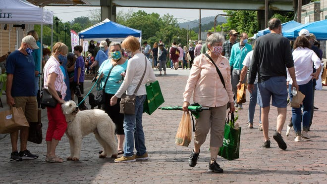 In this June 27 photo, visitors donning masks stroll down Main Street in Hendersonville.