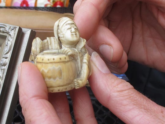 An antique ivory figurine is held by its owner, Ashley Prout McAvey of Shelburne. The piece was a gift from McAvey's grandmother.