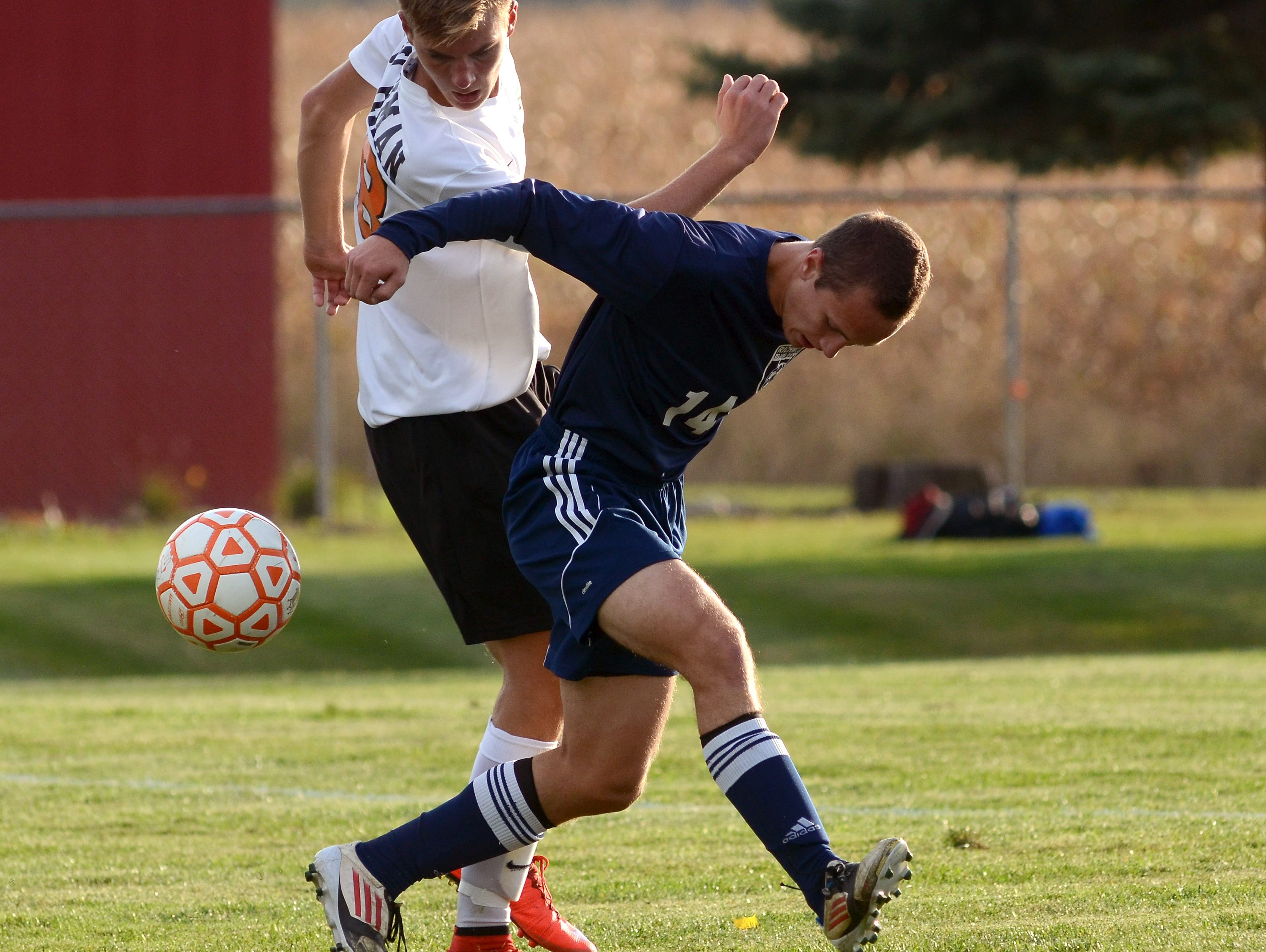 Blue Devils' Evan Quigley and Almont midfielder Zach Wichman both battle for the ball Monday, Oct. 12 during high school soccer action at Almont.