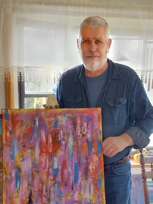 Jim Huff poses with his painting, Handywork, in his home studio.