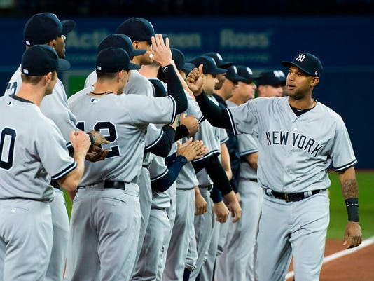 FILE - In this Thursday, March 29, 2018, file photo, New York Yankees center fielder Aaron Hicks, right, high-fives teammates as the Yankees and Toronto Blue Jays are introduced at an opening day baseball game in Toronto. The percentage of black players from the United States and Canada on opening-day active rosters has risen to its highest level since at least 2012. Major League Baseball attributed the increase at least partly to its efforts to increase baseball youth participation with programs that include Urban Youth Academies and Reviving Baseball in Inner Cities (RBI). Hicks played for an Urban Youth Academy team. (Nathan Denette/The Canadian Press via AP, File)