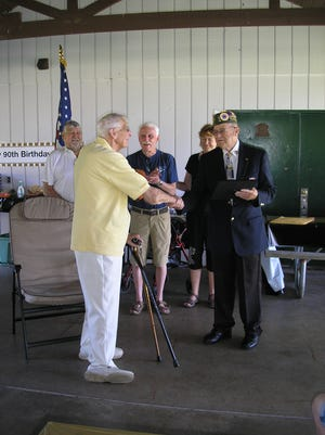Carl Harpke, left, accepts his letter of recognition from Joe Heilman, chairman of the Door County Veterans Service Council. In the background are fellow veterans and Harpke's family members.