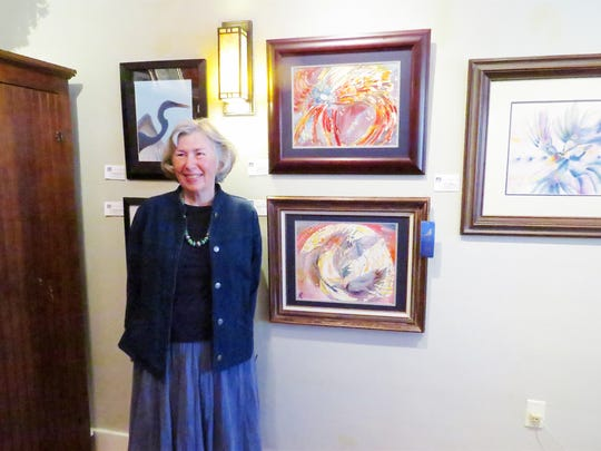 """First-place winner Connie Thibeau poses with her first place mixed media painting """"Blackbirds Singing in the Dead of Night."""""""