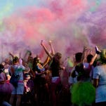 A runner holds up his arms as he is doused with color powder during the Color Craze 5K Friday, July 31, 2015 in Port Huron.