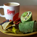This a veggie wrap with hummus, avocado, cucumbers, olives, carrots, onion, sprouts and lettuce, served here with a pumpkin spice latte, is a popular dish at Sun Shoppe Cafe in downtown Melbourne.