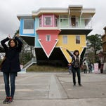 Visitors pose outside of an upside-down house created by a group of Taiwanese architects at the Huashan Creative Park in Taipei, Taiwan, Tuesday, Feb. 23, 2016. With a build price of $600,000 and over 300 square meters (3,230 square feet) of floor space filled with real home furnishings, the upside-down house will continue to be on display to visitors until July 22.
