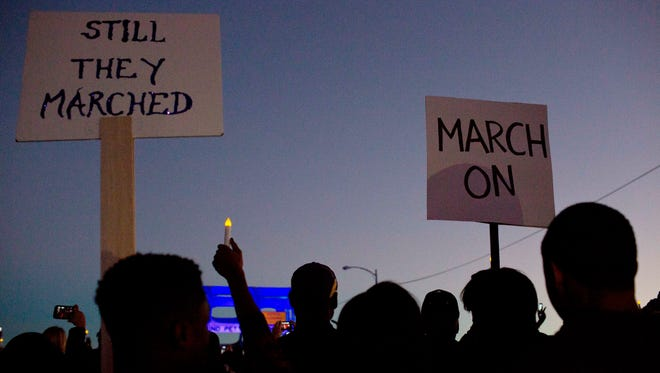 """Marchers hold up a """"March On"""" and """"Still They Marched"""" signs as they make their way towards the Edmund Pettus Bridge in honor of Martin Luther King Jr., Sunday, Jan. 18, 2015, in Selma, Ala."""