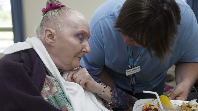 Karen Wininger, 75, receives help during lunch in August at the Davis Center, a  nursing home near Bloomfield.