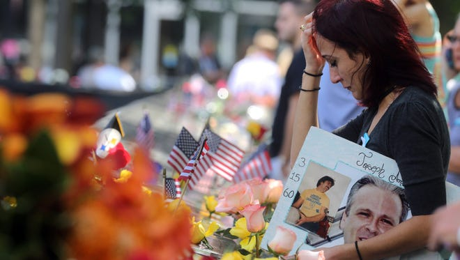 Mercedes Arias, 26, of Yonkers holds a photograph of her father, Joseph Amatuccio of Queens as she attends a ceremony marking the 15th anniversary of the 9/11 attacks at the Sept. 11 Memorial at the World Trade Center in New York City. Arias was 11 years old when her father was killed in the attacks.
