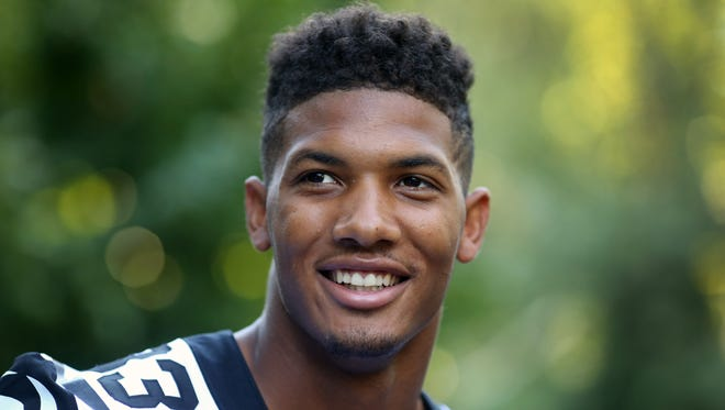 """Cincinnati Bengals Tyler Boyd, rookie wide receiver, visited the Cincinnati Zoo and Botanical Garden's white tiger exhibit to debut the Bengals white and black-accented """"Color Rush"""" uniforms they'll wear when they play the Miami Dolphins Sept. 29. He was joined by Carlos Dunlap, defensive end and All-Pro defensive tackle Geno Atkins."""