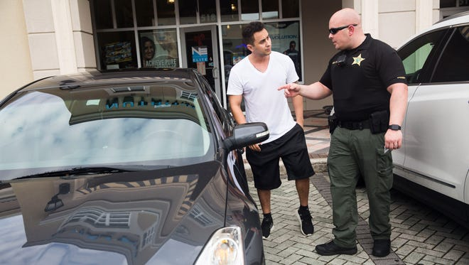 Sgt. Tom Orr talks to Kenneth Gallego, of Naples, about leaving his wallet visible in his car in the parking lot of the Shoppes at Vanderbilt on Wednesday, Jan. 4, 2017. The burglary prevention initiative was conducted by the Collier County Sheriff's Office.