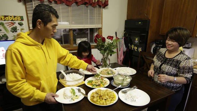 Wai Hinn Oo and Nang Shwe Thein serve the family dinner, and Christina, 7, waits for her plate. They have another daughter 15-month-old Victoria. They will be celebrating their five-year anniversary coming to the United States. Hinn, Thein and Christina came to the United States from Malaysia and ended up in Oshkosh with the help of World Relief Fox Valley. Hinn has had a few jobs and is currently working at Bemis, where he was a machine operator and now is a technician. The family rented an apartment when they first came to Oshkosh. Now they own their own home on the north side of Oshkosh. Hinn is going to Fox Valley Technical College part-time, and both want to take their citizenship test to become U.S. citizens.