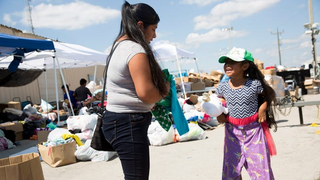 Lorena Jimenez, left, smiles as her daughter Marabel, 5, tries out a pair of pants that were available for donation outside of the Everglades City Fire Station 60 on Monday, Sept. 18, 2017, in Everglades City, Fla. Recovery efforts began to escalate as federal and state agencies start to rally their efforts toward the small community that was severely struck by Hurricane Irma last Sunday.