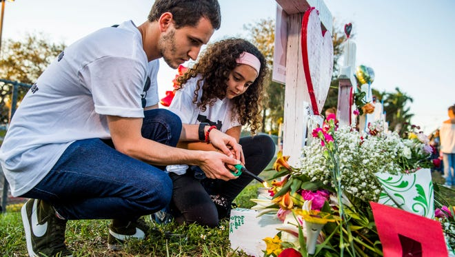 Camila Valladares, 9, and brother Miguel Piacquadio, 25, light a candle at a memorial outside Marjory Stoneman Douglas High School in Parkland, Fla., on Feb. 18, 2018, in response to a shooting at the high school on Feb. 14 that took 17 lives.