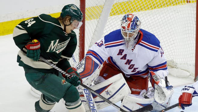 A scoring attempt by the Minnesota Wild's Mikael Granlund, left, is broken up as Rangers goalie Cam Talbot defends the net Thursday night.