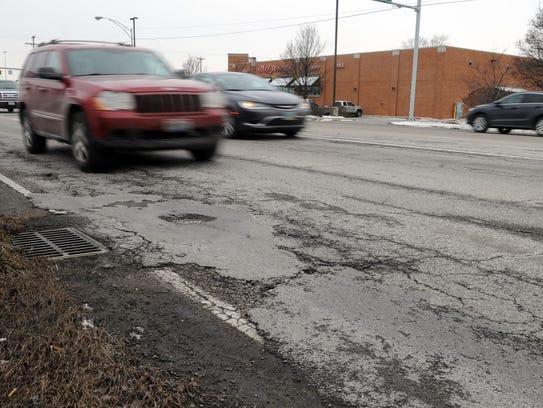 People drive by potholes Friday on Bridge Street north