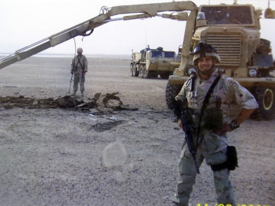 Scott Lewis of Carlisle with an excavating truck during his deployment to Iraq.
