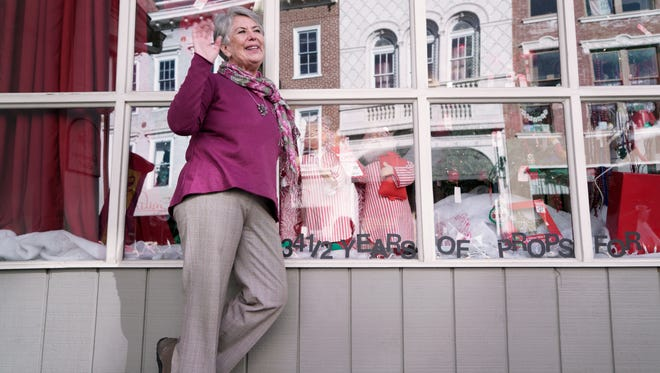 Shirley Robinson, who will soon be closing Grandma's Bait in downtown Staunton, waves to a passerby outside her shop while standing for a portrait on Tuesday, Nov. 24, 2015.