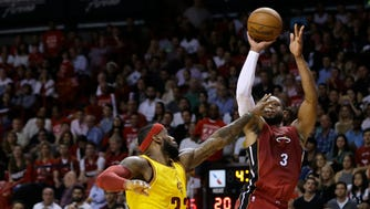 Heat guard Dwyane Wade (3) shoots over Cavaliers forward LeBron James.