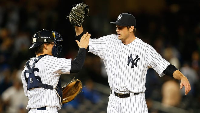 Andrew Miller high-fives catcher John Ryan Murphy after closing the Yankees' 6-4 win Sunday night. Miller is perfect in seven save chances.